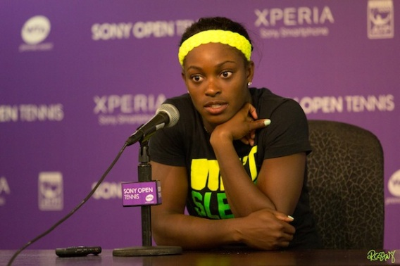 Sloane Stephens is sitting at a table, there is a microphone sitting in front of her. She is wearing a bright yellow headband and black shirt with bright neon letters on it. Because her left elbow is on the table and her left hand is under her chin, you cannot read her shirt. Her other arm is in front of her body, resting on the table. She appears to be listening to a reporter.